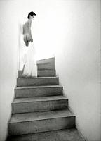 Naked young woman going upstairs