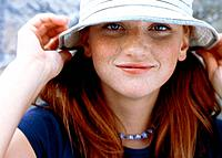 Young woman with freckles wearing a hat