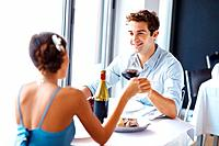 Handsome young man toasting wine with his girlfriend at the restaurant smiling