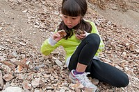 A young girl carefull studies rocks for signs of fossils at the Macabee Fossil beds west of Kamloops, Thompson Okanagan region of British Columbia, Ca...