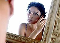 Young woman putting some makeup on in front of a mirror