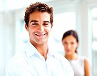 Portrait of handsome young man smiling with a female in background
