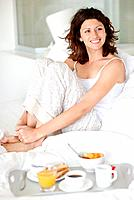 Pretty woman sitting on bed and smiling with a tray of breakfast in foreground