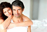 Middle aged happy couple sitting together on bed _ Copyspace