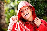 Pretty young female holding a red raincoat hat on head and enjoying the rain _ Outdoors