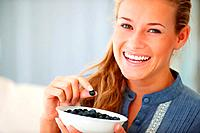 Portrait of smiling teenage female eating blackberries at home _ Indoors