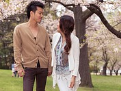 Young happy Asian couple walking in a park under blooming cherry trees