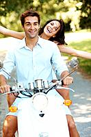 Portrait of happy young love couple on scooter enjoying themselves in a park