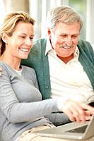 Smiling mature woman showing something interesting on laptop to her father