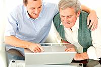 Happy mature man teaching his father to use a laptop
