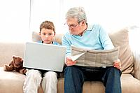 Old man sitting with a newspaper while a little boy using a laptop _ Indoor