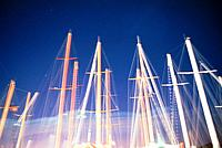 Masts of sailing boats in front of a blue sky