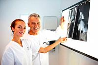 Portrait of smiling doctors examining an x_ray over light