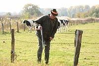 hunter climbing over the barbed wire fence at a pasture, Germany