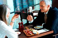 Portrait of mature couple toasting wine and celebrating their anniversary at a restaurant