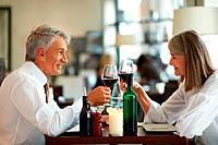 Mature couple sitting at restaurant table toasting wine glasses