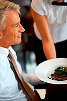 Happy senior man at restaurant with a waitress serving food