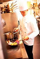 Portrait of smart male chef cooking food in commercial kitchen