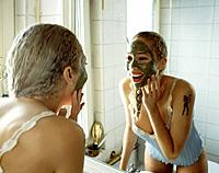 Young Woman Putting on Facial Cream
