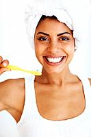 Portrait of beautiful mixed race woman with bright smile brushing teeth