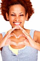 Smiling young lady making a heart shape sign by hands against white