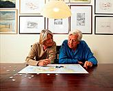 Senior Couple Doing Jigsaw Puzzle at Table