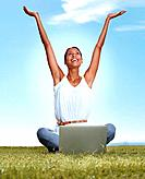 Portrait of a happy young woman with raised hands and using laptop sitting on the grass