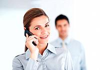 Closeup of beautiful business woman using cell phone with blur colleague in background