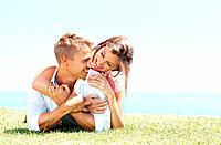 Portrait of couple enjoying nature together while lying on grass