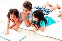 Three cute siblings doing home work together while lying on floor