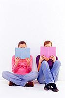 Two teenage girls sitting with books on floor