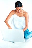 Happy mixed race woman relaxing at home while using laptop