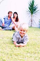 Boy lying on lawn, parents sitting in background