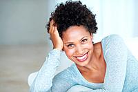 Portrait of attractive African American woman smiling while lying on couch