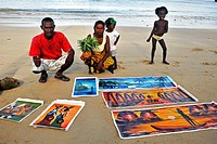 paintings for sale lying on sandy beach, Madagascar, Nosy be