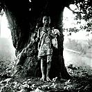 Barefooted boy standing under a tree