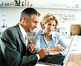 Businessman and Businesswoman Using Laptop in Kitchen