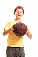 Portrait of a happy small child standing with basketball against white background