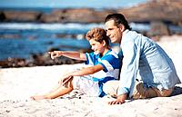Cute little boy pointing at the sea while sitting at tthe beach with his father _ Copyspace