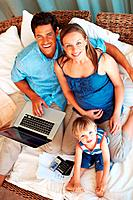 High angle view of family sitting on sofa using laptop and smiling