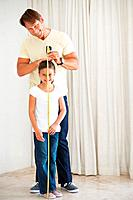 Full length of father measuring the height of his daughter using a measuring tape