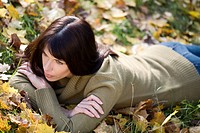 young woman pondering while lying on the belly on grass covered with autumn leaves