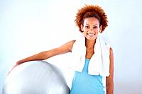 Portrait of young female fitness instructor holding a pilates ball and smiling