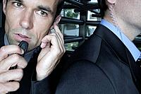 Two businessmen listening to earpieces