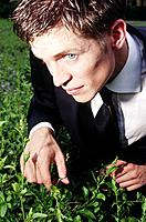 Young man trimming hedge with manicure scissors