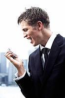 Young man wearing suit yelling at mobile phone in his hand