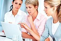 Portrait of a smart young businesswoman using laptop with his colleagues at office