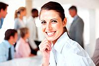 Closeup portrait of a smiling young businesswoman and her collleagues working behind at office