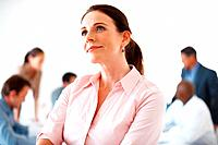 Smiling female executive thinking of new ideas with colleagues in background