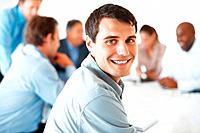 Closeup portrait of smart young business man sitting with colleagues and smiling during meeting